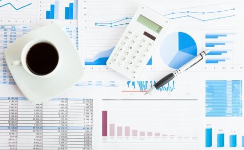 Filiżanka kawy, kalkulator, długopis i statystyki