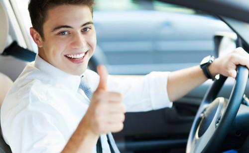 Zadowolony młody chłopak w białej koszuli z krawatem prowadzący samochódz