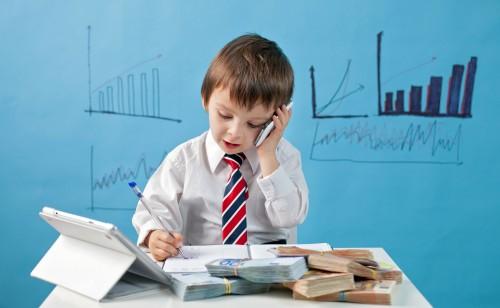 Pliki pieniędzy i małe dziecko rozmawiające przez telefonm