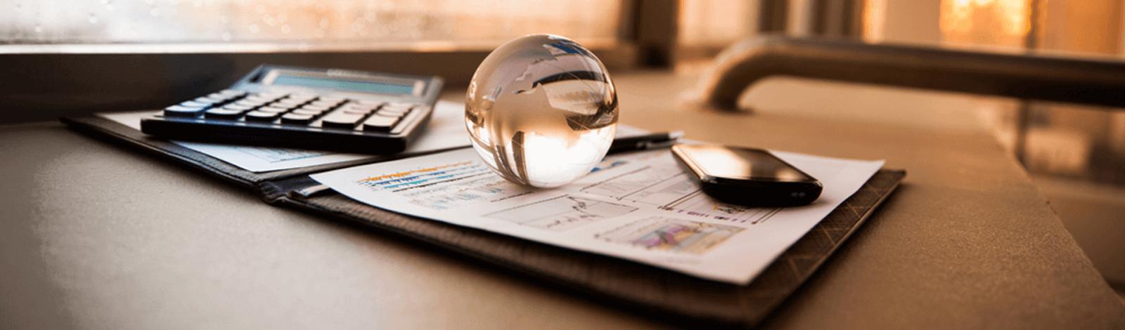 Kalkulator, teczka, szklana kula i telefon w biurze księgowym
