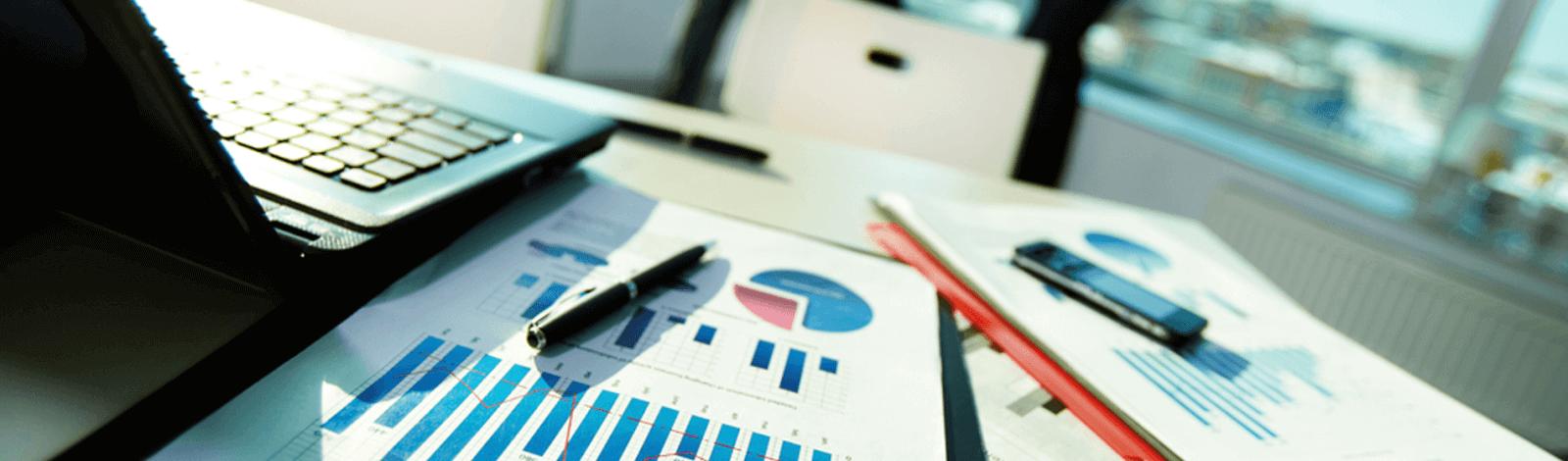 Komputer, statystyki i długopis na biurku